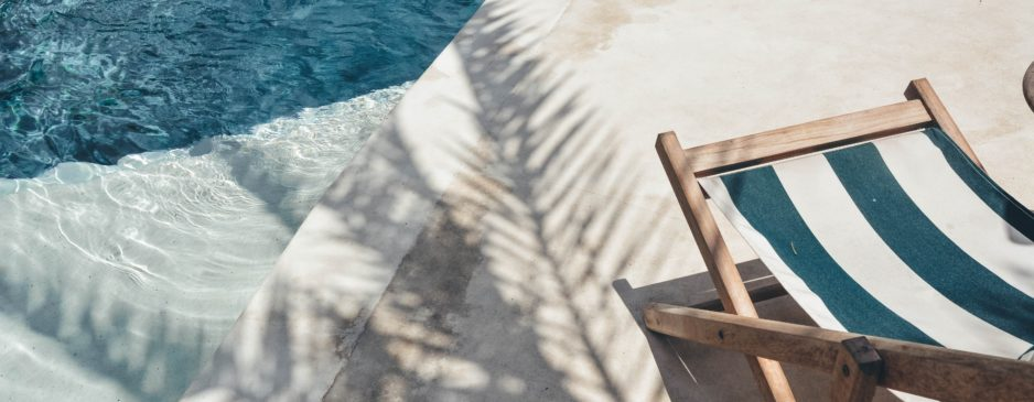 Transat en bois assise tissu rayée turquoise et blanc en bord de piscine